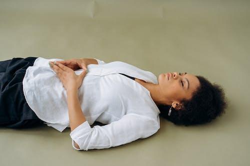 Woman in White Long Sleeve Shirt Lying on Floor