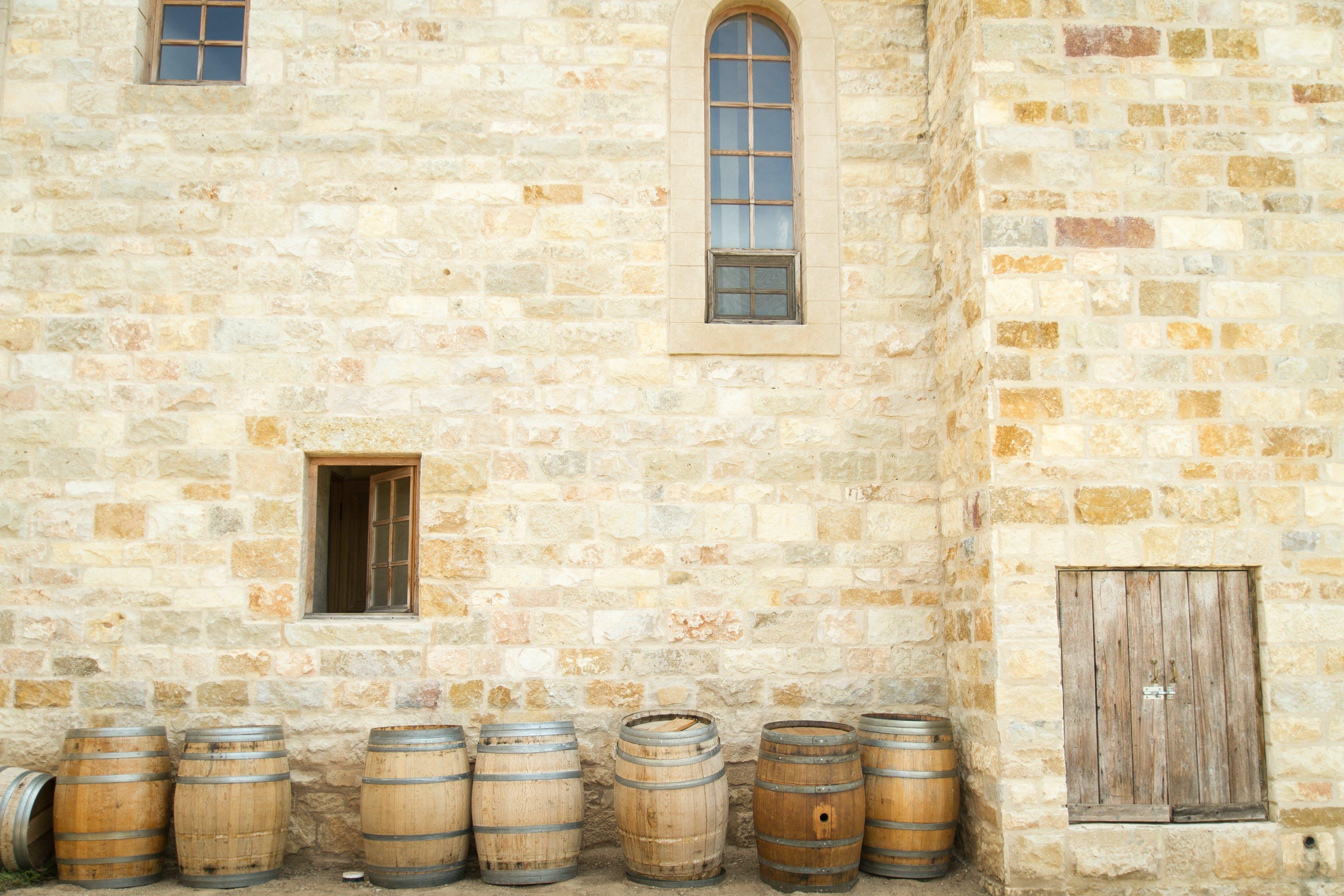 Wooden Barrels Beside Shingle Wall