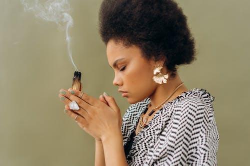 Woman in White and Black Shirt Smoking