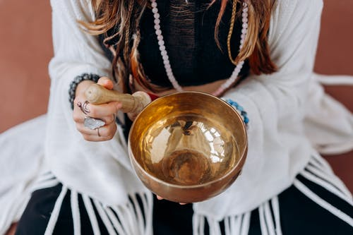 Woman in White Long Sleeve Shirt Holding Gold Round Bowl