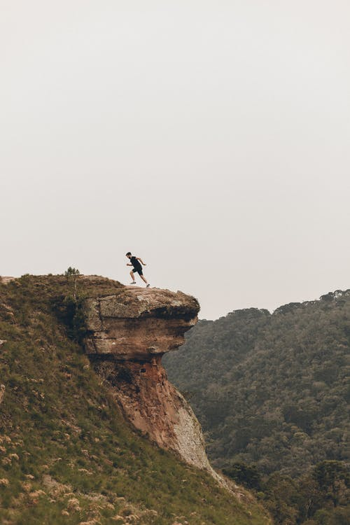 Person Jumping on Brown Rock Formation