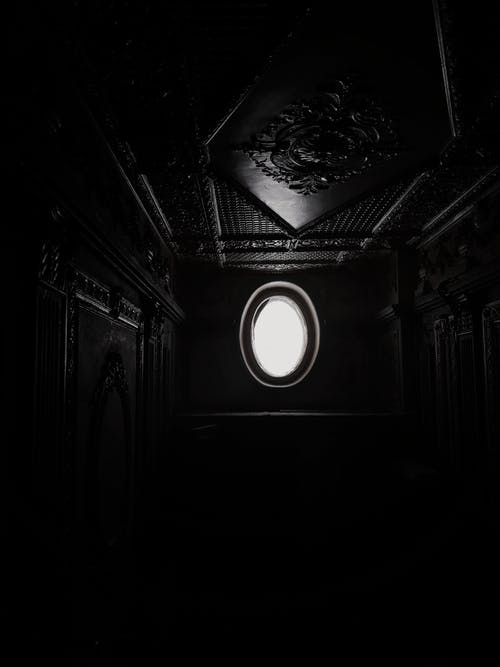 Black and white of long narrow dark corridor with light coming from window and ornamental elements on ceiling and walls