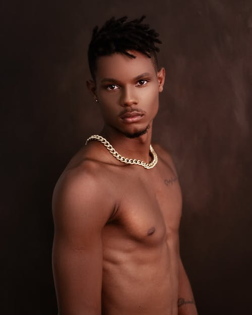 Shirtless muscular African American male with short dark hair standing in studio and looking at camera against brown background