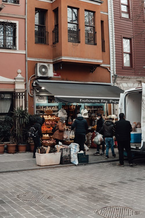 Customers buying food products in street shop near old building and car in city