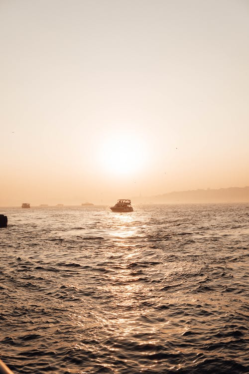 Wavy sea with sailing boats in sunset