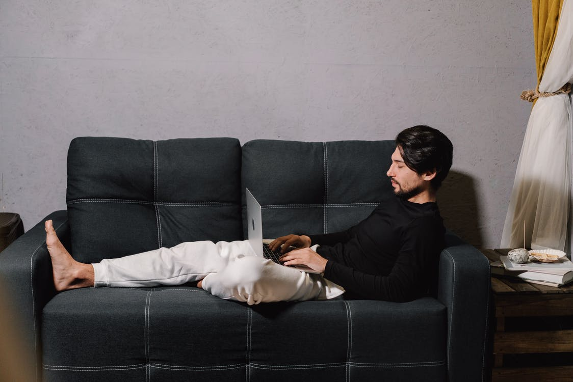 Man in Black Sweater Lying on Gray Couch