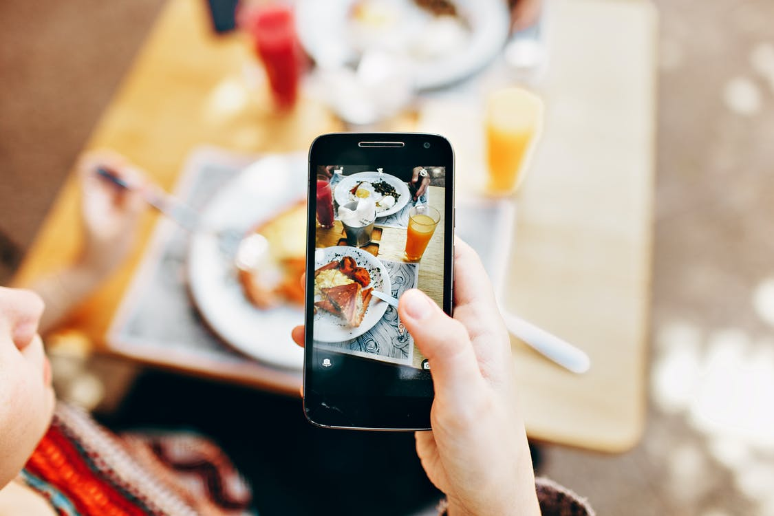 Person Holding Phone Taking Picture of Served Food