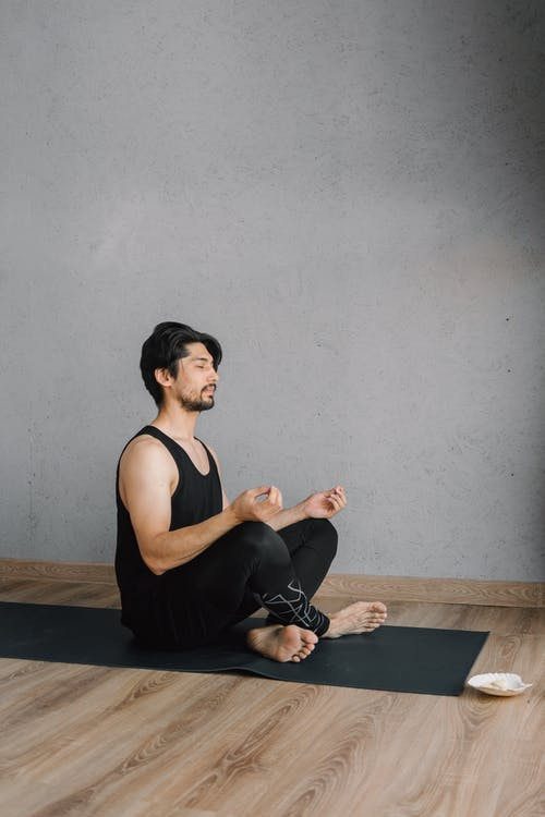 A Man in Black Activewear Doing a Meditation on a Yoga Mat