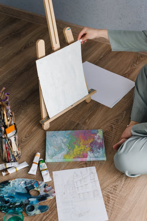 Person Sitting On Floor Holding A Canvas