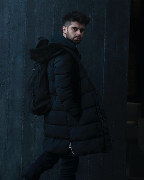 Man in Black Bubble Jacket Standing Near Gray Wall