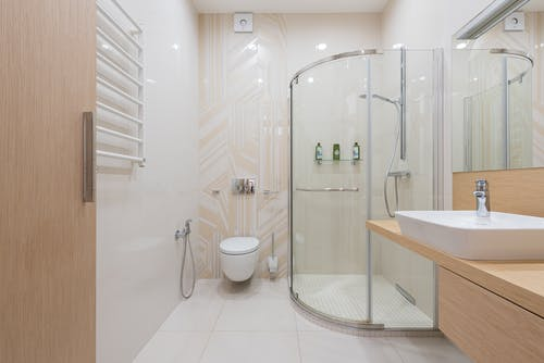 Interior of spacious light bathroom with shower cabin and wooden furniture