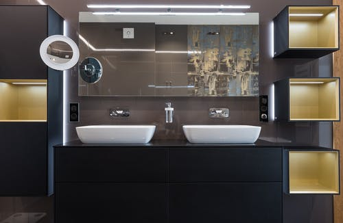 White sinks placed on wooden cabinet in contemporary illuminated bathroom