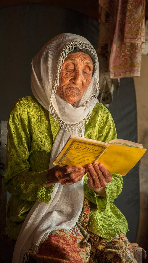 Elderly ethnic female in traditional apparel with ornament reading textbook while sitting in daytime
