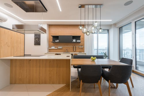 Interior of contemporary large clean kitchen with wooden cabinets and white counter under modern lights in apartment