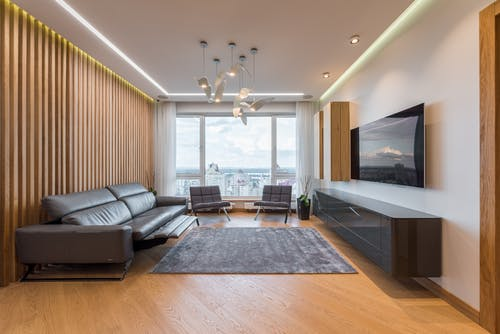 Modern spacious interior of lounge with TV and leather sofa