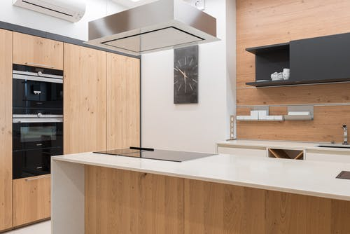 Contemporary kitchen with black clock and cupboard with white utensil