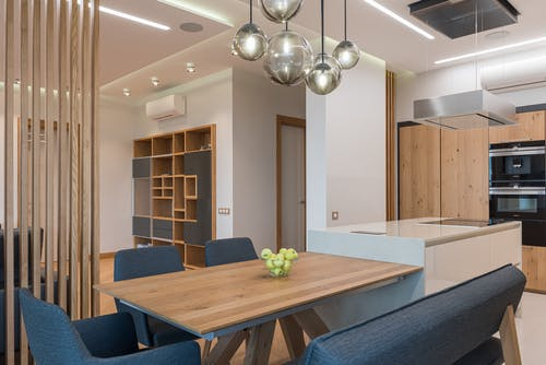 Brown table surrounded with blue chairs in dining room with modern interior and timber shelves