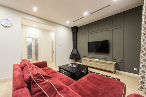 Interior of modern large living room with TV hanging on gray wall illuminated with bright lamps