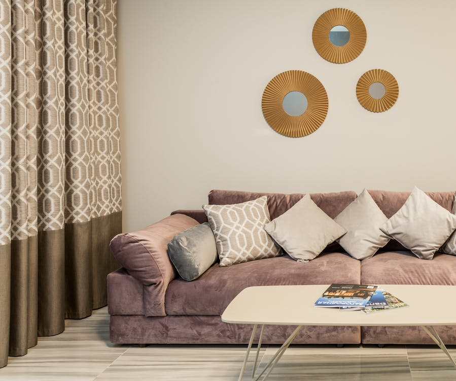 Cozy sofa decorated with many cushions near table with magazines in lounge with curtains