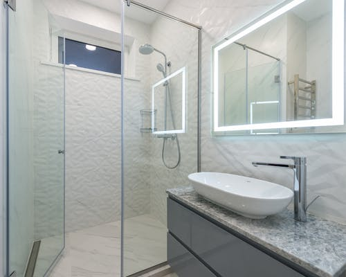 Stylish mirror illumination shining in bathroom above sink with faucet and shower cabin