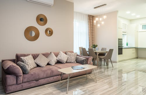 Modern interior design of flat with comfortable couch in stylish living room with kitchen equipped with built in appliances