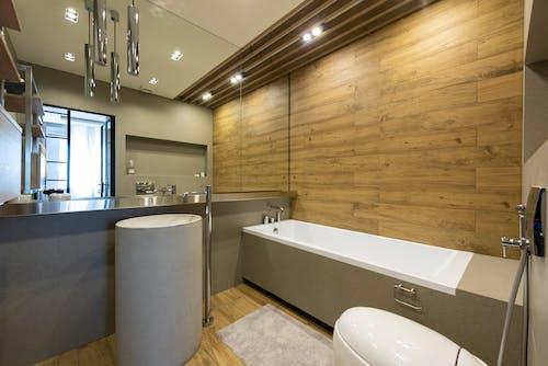 Interior of stylish bathroom with toilet round sink and bathtub