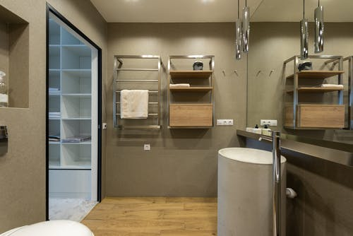 Interior of contemporary bathroom with towel hanging on rack under lights on ceiling with sink near mirror