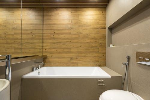 Stylish bathroom with modern bathtub and bidet shower