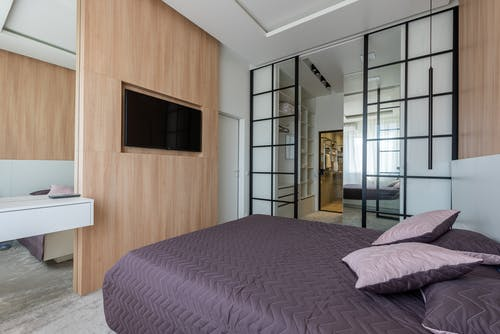 Interior of big bed covered with blanket and cushions in bedroom with opened glass doors