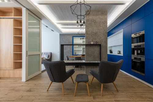 Interior design of contemporary kitchen with comfortable armchairs and blue cupboards with appliances under shiny ceiling illumination
