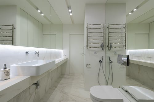 Modern restroom with sink under mirror and toilet