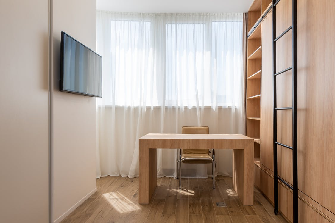 Chair and wooden table placed near window with curtains in home office with TV set