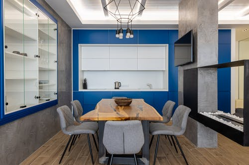 Interior of modern kitchen with cupboards and TV set with chairs placed around wooden table
