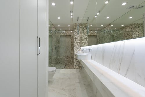 Contemporary restroom with marble tile and toilet behind glass wall with sink under mirror