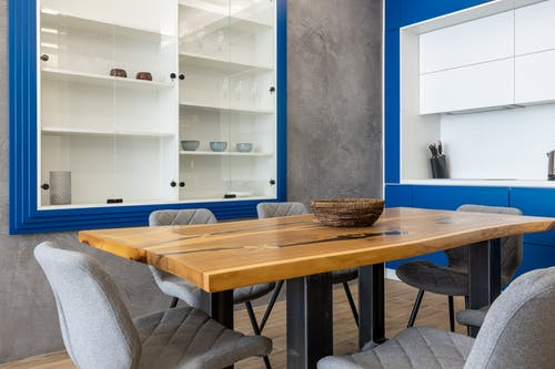 Interior design of modern kitchen with wooden dining table with chairs among cabinets on walls