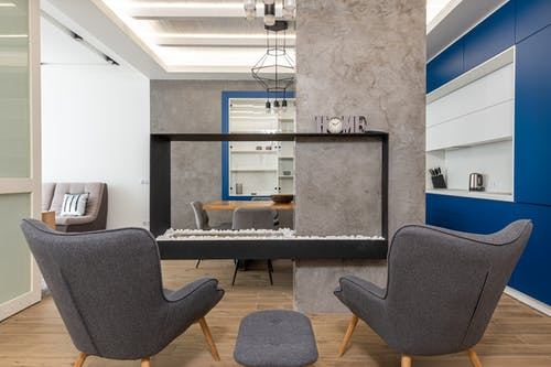 Interior of modern apartment with armchairs in kitchen