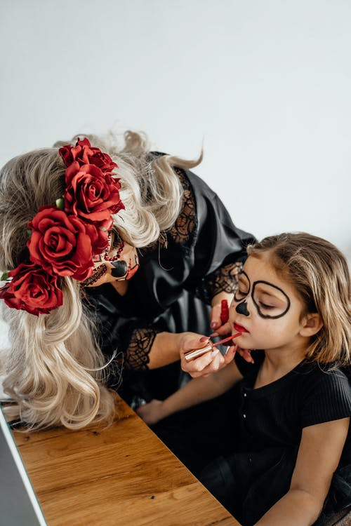 Woman in Black Dress Applying Red Lipstick On A Girl