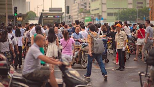 Unrecognizable Asian citizens walking on urban pavement
