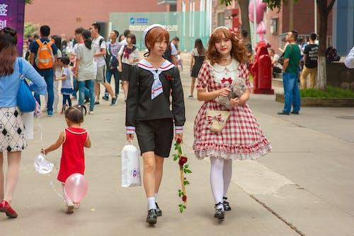 Asian girlfriends in retro wear walking on city street