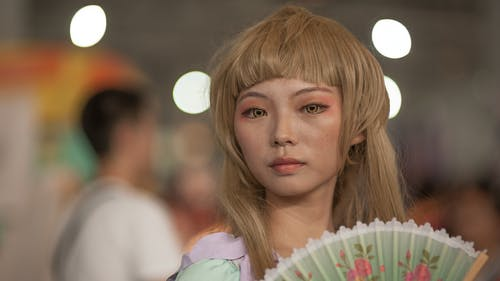 Asian woman in wig with open fan