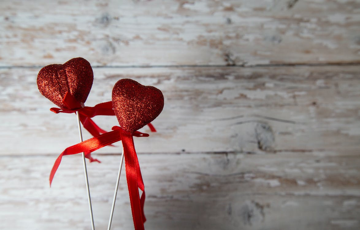 Red hearts on sticks against wooden background