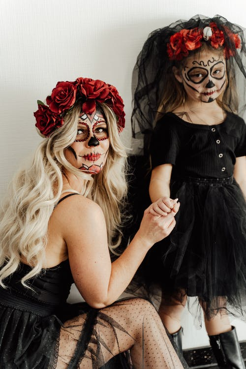 Mother and Daughter in Halloween Costume Looking at the Camera