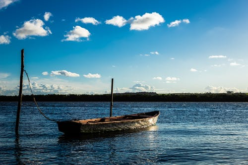 Brown and White Boat on Sea Under Blue Sky