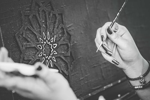 Black and White Photo of Hands Holding a Paintbrush