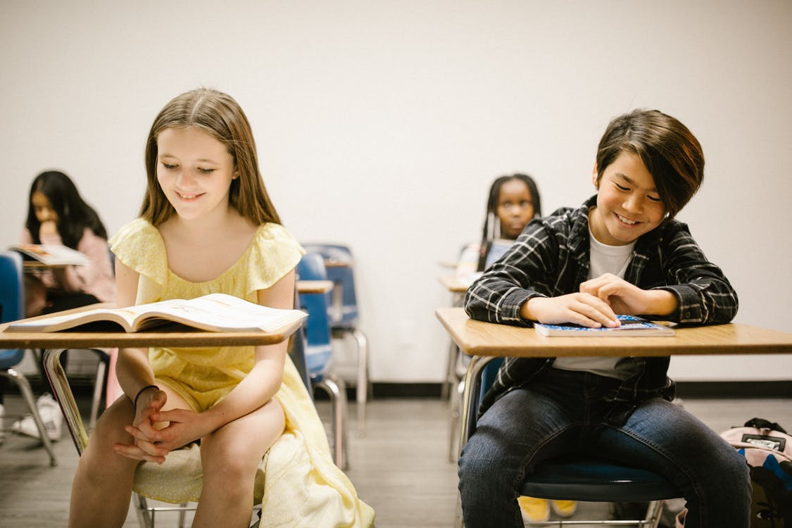 Two Students Smiling While Sitting on Their Desk