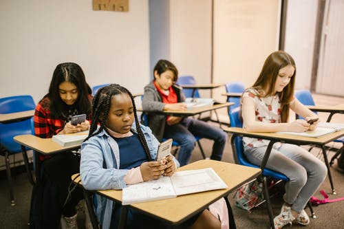 Students Sitting Inside the Classroom While Using Their Smartphone