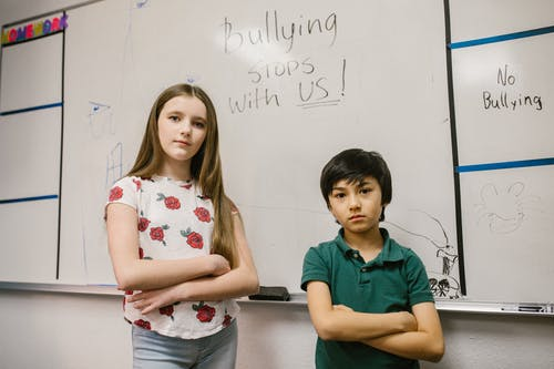 Two Kids Standing by the White Board