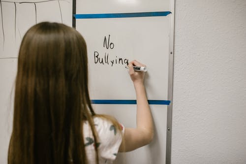 Girl Writing a Message Against Bullying on a White Board