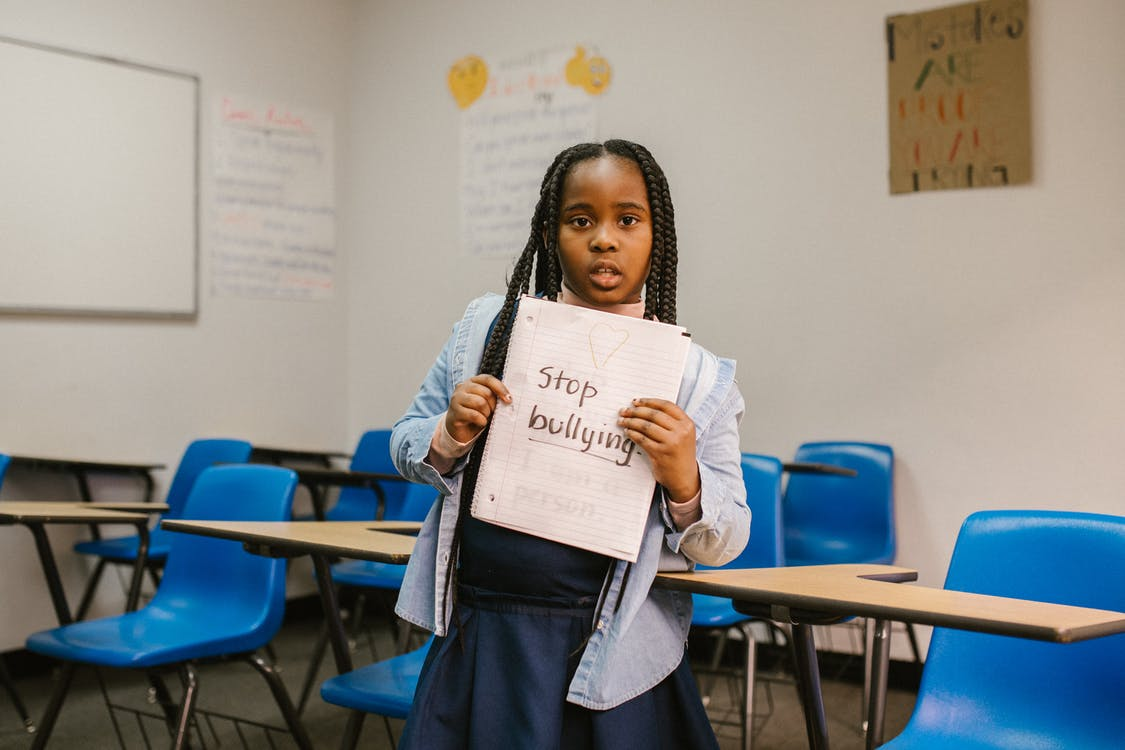 Girl Showing a Message Against Bullying Written in a Notebook