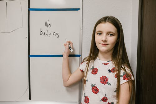 Girl Showing a Message Against Bullying Written in White Board